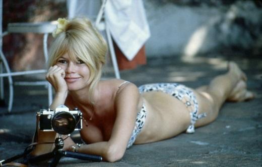 """Jour de repos pour Brigitte BARDOT au MEXIQUE pour le tournage du film """"VIVA MARIA"""" de Louis Malle : attitude souriante de l'actrice en maillot de bain, allongée sur le sol de sa maison au coeur même de CUERNAVACA, à 500 m du Zocalo - la place centrale, un appareil photo posé sur un petit pied devant elle."""