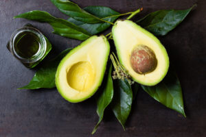 Avocado with leaves and jar of oil on black background. top view