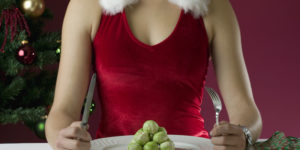 Female in Christmas outfit eating brussels sprouts